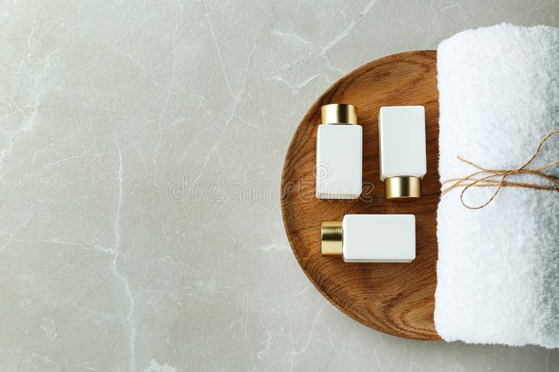 Top view of wooden tray with cosmetic bottles and towel on grey marble table, space for text. Spa treatment. Top view of wooden tray with cosmetic bottles and stock photos