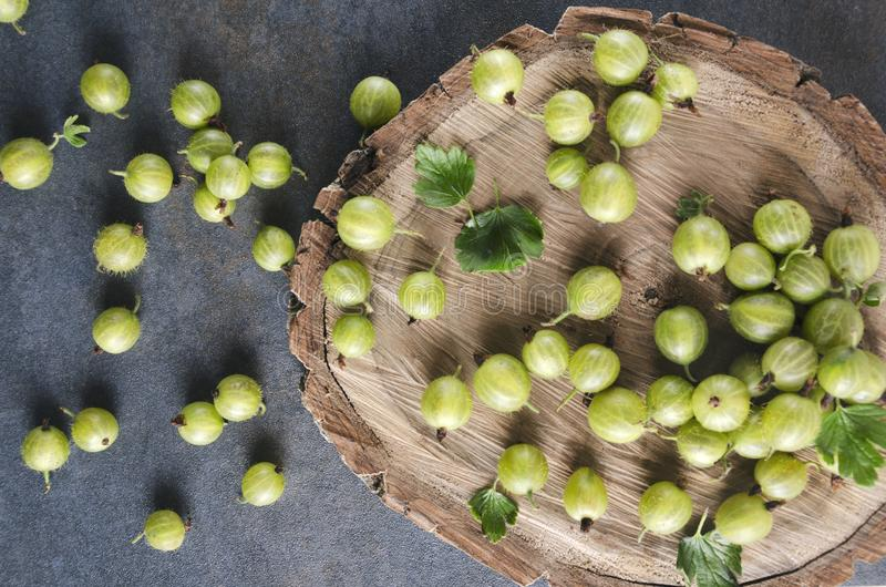 Top view of wooden tray and gooseberries on it, rustic style. Closeup of fresh harvest of gooseberries on the wooden surface.Great heap of fresh and sweet summer royalty free stock photo