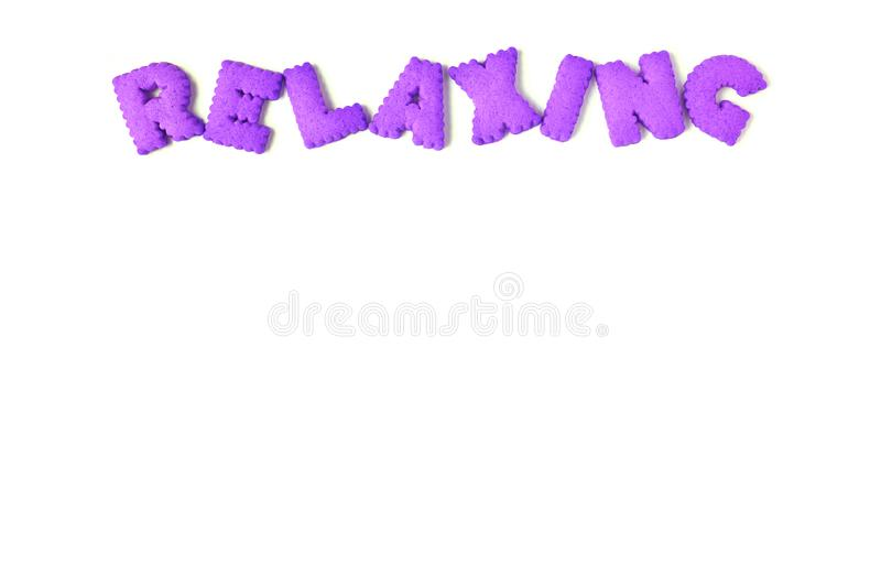 Top view of the word RELAXING spelled with purple color alphabet shaped cookies on white background. With free space stock photo