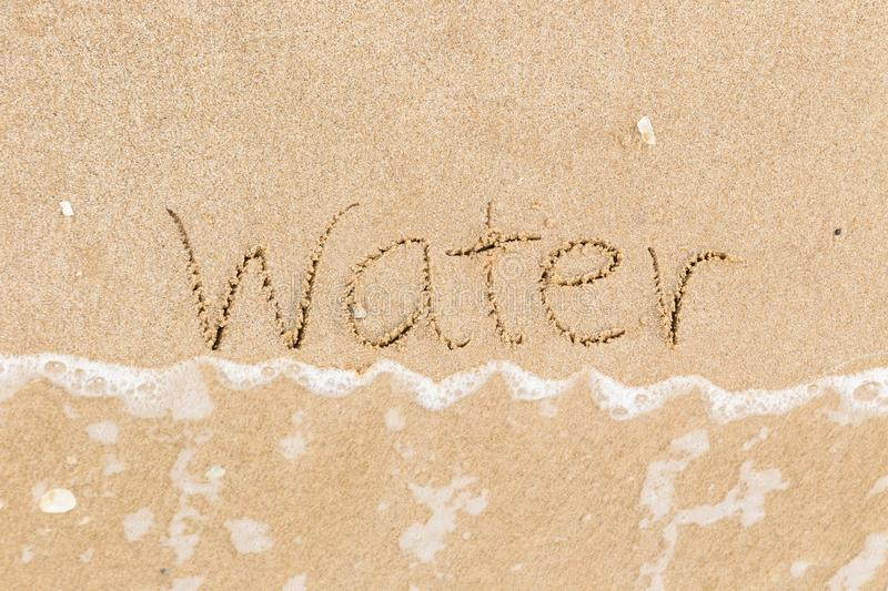 The word Water in sand beach with wave. Top view of the word Water written in sand beach with foam wave in background, Natural daylight in summer season stock images