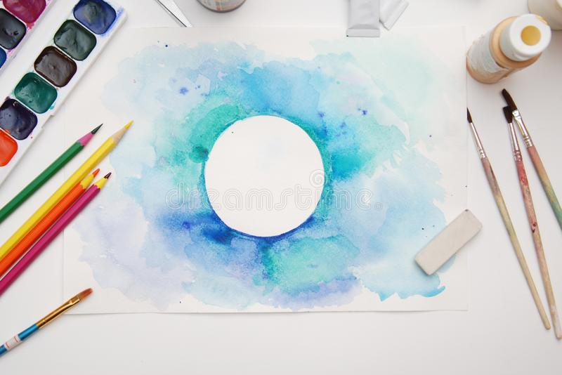Top view of Work Process Blank Watercolor Paper pad, Watercolor Painting Supplies, Brushes and Colorful Pencil. Creation process o. F watercolor painting royalty free stock photos