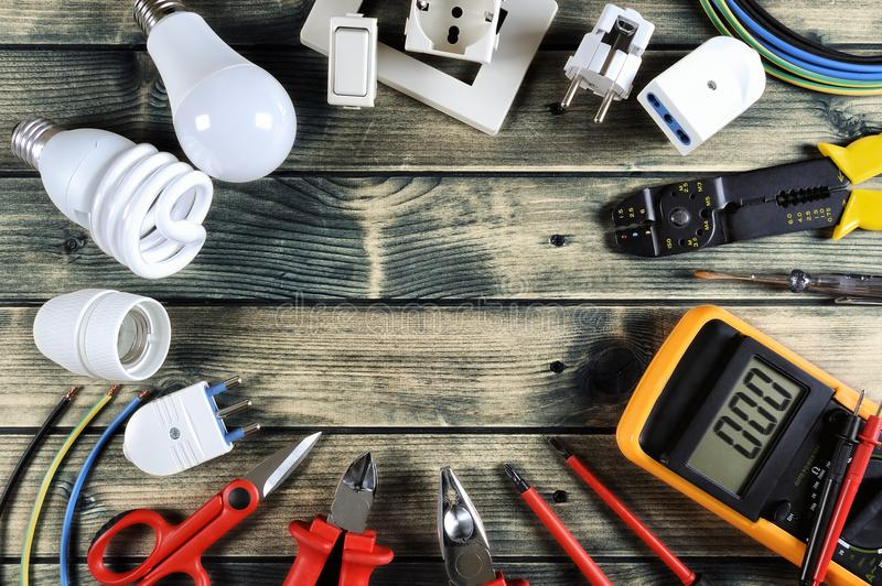 Top view of work tools and electrical system components on rustic wooden background royalty free stock photo