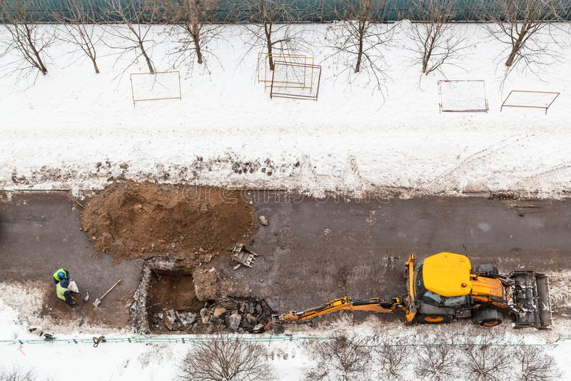 Top view of workers and excavator digging road royalty free stock image
