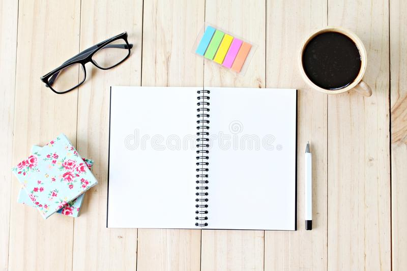 Top view of working desk with blank notebook with pen, coffee cup, colorful note pad and eyeglasses on wooden background stock images