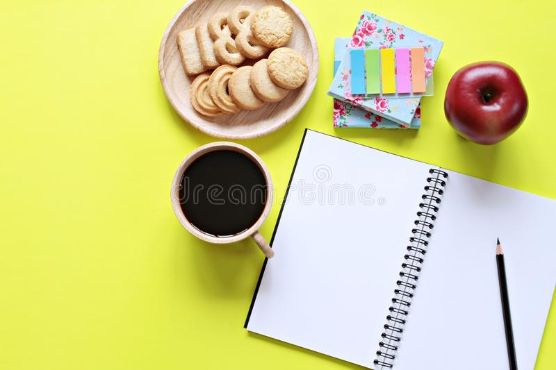 Top view of working desk with blank notebook with pencil, cookies, apple, coffee cup and colorful note pad on yellow background royalty free stock image