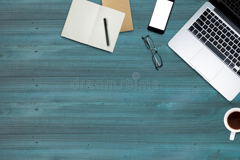 \'Top view, Working desk, computer, laptop, smart phone, coffee mug, glasses and notebooks on wooden blue pastel color with textur stock image