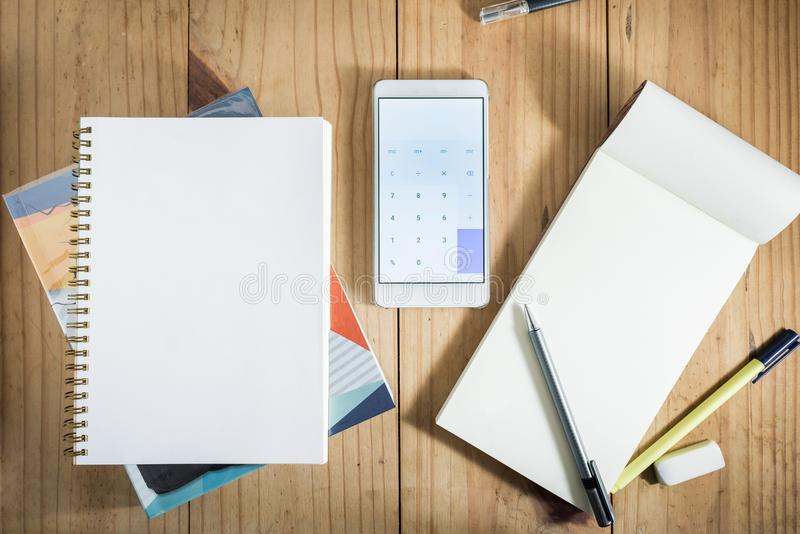 Top view of working object : gray pencil on notebook and white smartphone open calculator app on wooden table stock photo