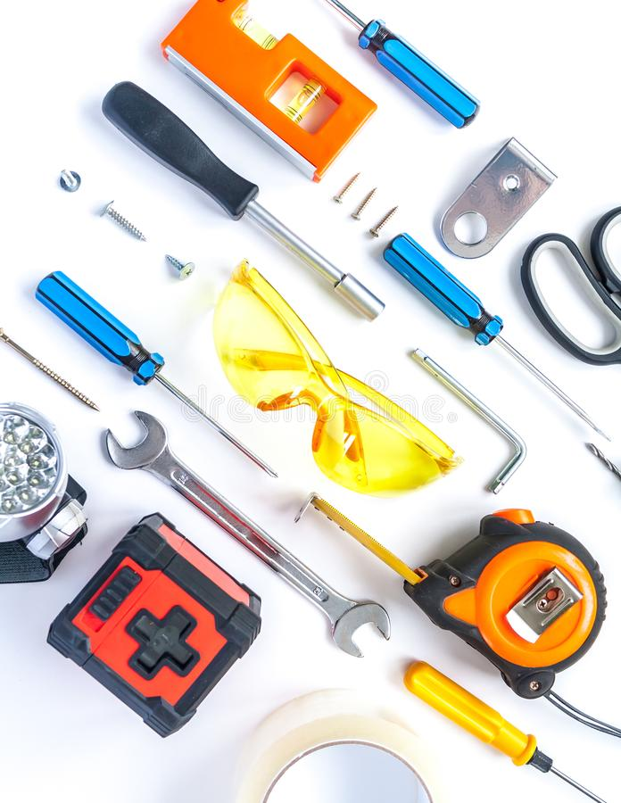 Top view of working tools, wrench, screwdriver, level, tape measure, bolts, and safety glasses on a white background. royalty free stock photo