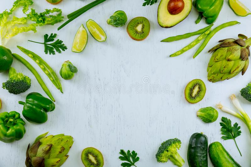 Variety green vegetables and fruits on a wooden table top view workplace cook with fresh royalty free stock photography