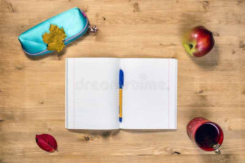 Top view workspace of the student with opened copybook, case, pen, apple, autumn maple leaf, markers, cup tea, on desk. Workspace of the student with opened stock images
