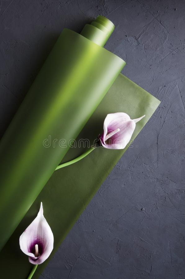 Top view of wrapping paper and callas flowers.Concept of decoration and wrapping gifts, flowers. View from above of callas flowers on the green wrapping paper royalty free stock image