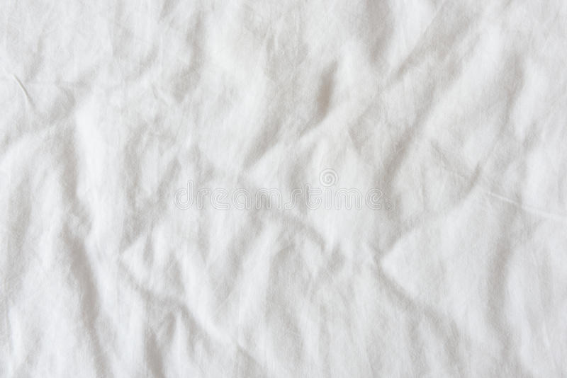Top view of wrinkles and spring embossed pattern on a white messy bed sheet. stock photography