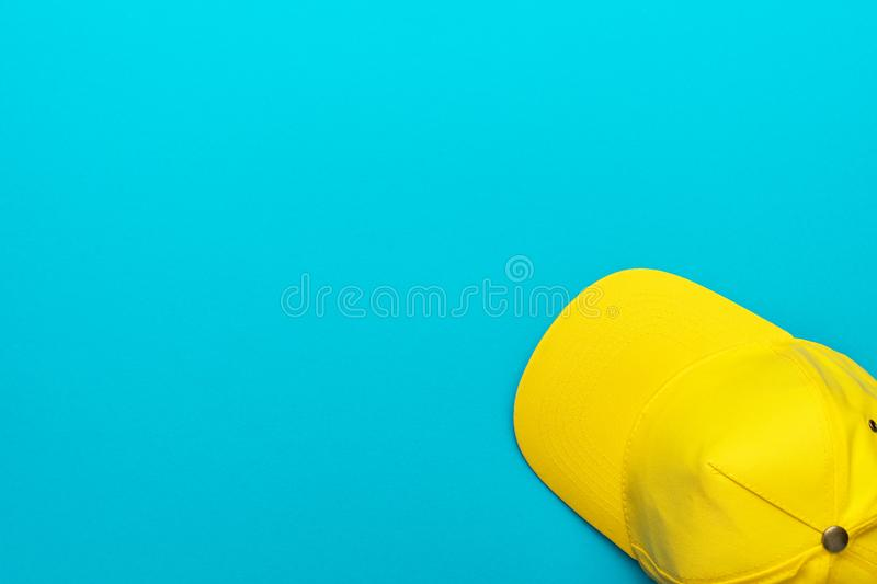 Top view of yellow baseball cap over blue turquoise background with copy space. Minimalist flat lay photo of the bright yellow cap with copy space. Top view of stock photos