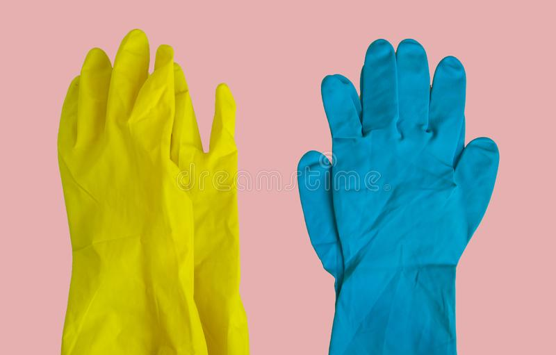 Top view of yellow and blue rubber protective gloves on pink table for spring or daily cleaning. The concept of a commercial stock photos