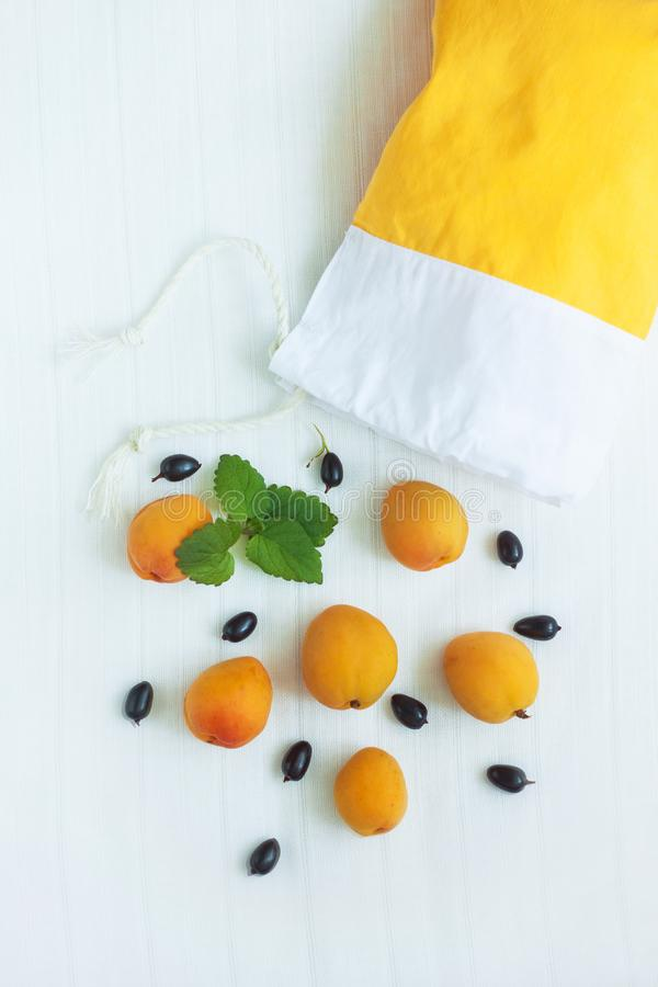Top view of yellow cotton shopping bag with organic eco apricot fruits on white linen background. Zero waste. Cotton shopping bag with apricots,black currents royalty free stock photo