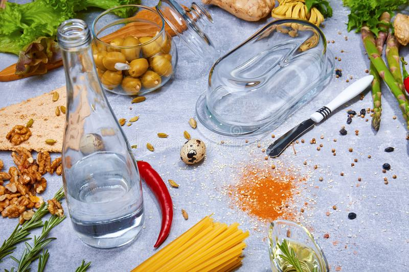 Close-up of a gray table with pasta, a bottle, red chili pepper, walnuts, olives, asparagus on a light gray background. royalty free stock photo
