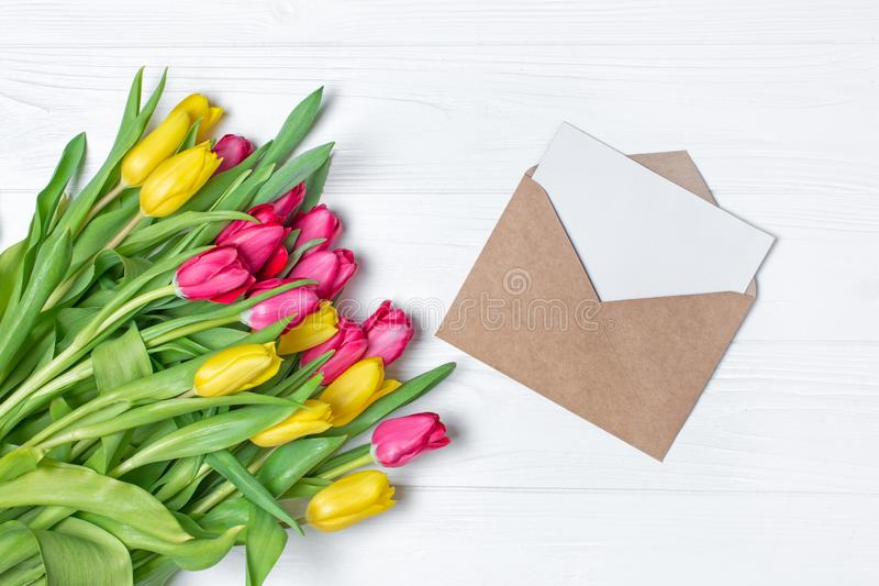 Top view on yellow and pink tulips bouquet with mockup of greeting card in kraft envelope royalty free stock photos