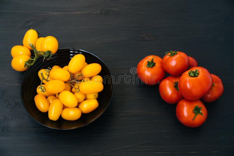 Top view of yellow and red cherry tomatoes in black bowl on wooden background stock photos