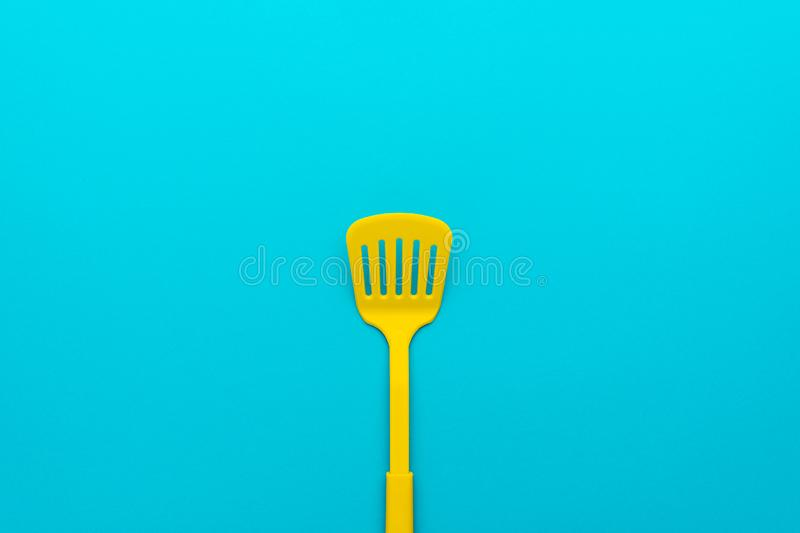 Top view of yellow slotted spatula on turquoise blue background with copy space. Top view of plastic kitchen utensil. Minimalistic flat lay image of yellow stock images