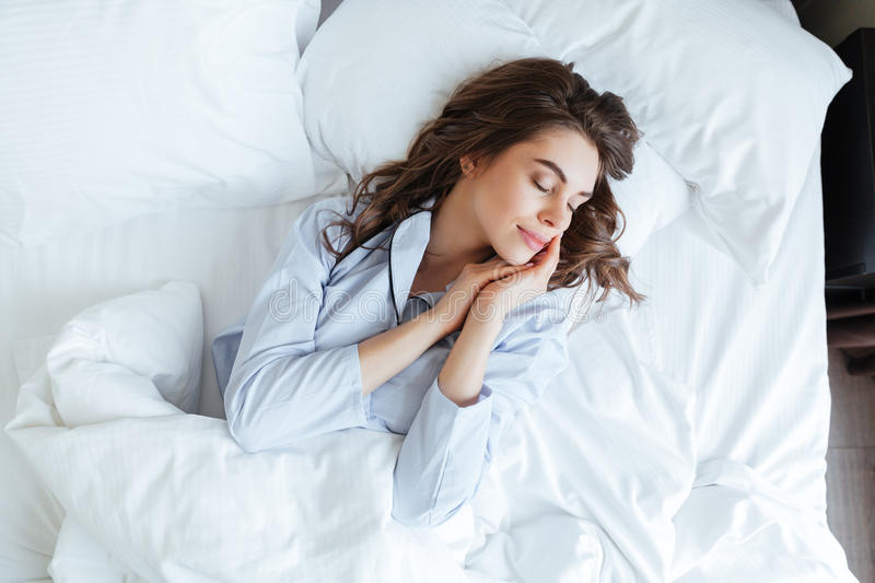 Top view of young beautiful woman in pajamas sleeping peacefully. In bed at home royalty free stock photos