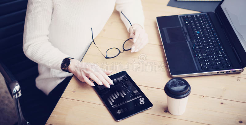 Top view of young beautiful woman working at the wooden table with mobile devices.Female hand touching digital tablet. Graph and diagram on display.Horizontal royalty free stock photo