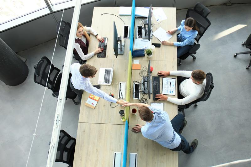 Top view of young business partners shaking hands over deal at office. Focus on hand shake. royalty free stock photography