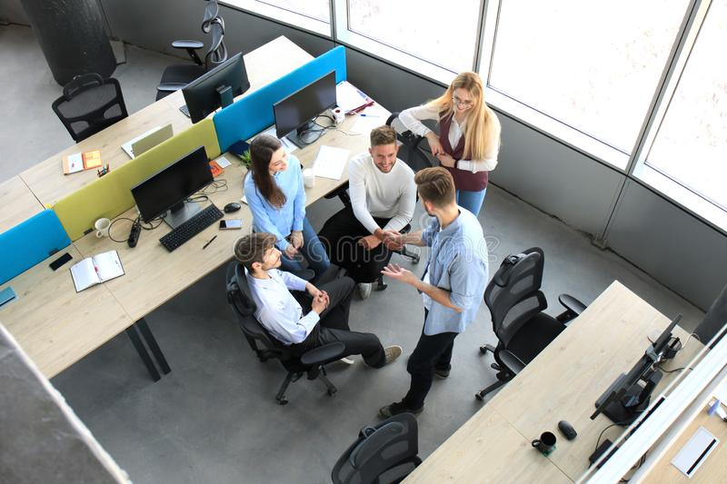 Top view of young business partners shaking hands over deal at office. Focus on hand shake. royalty free stock image