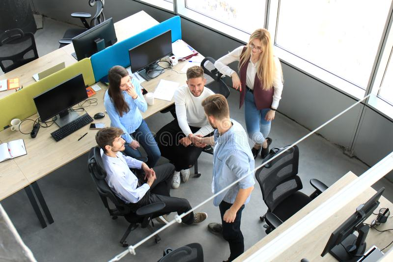 Top view of young business partners shaking hands over deal at office. Focus on hand shake. stock photography