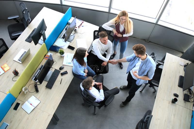 Top view of young business partners shaking hands over deal at office. Focus on hand shake. stock photos