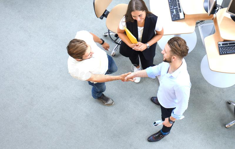 Top view of young business partners shaking hands over deal at office. Focus on hand shake. royalty free stock photos