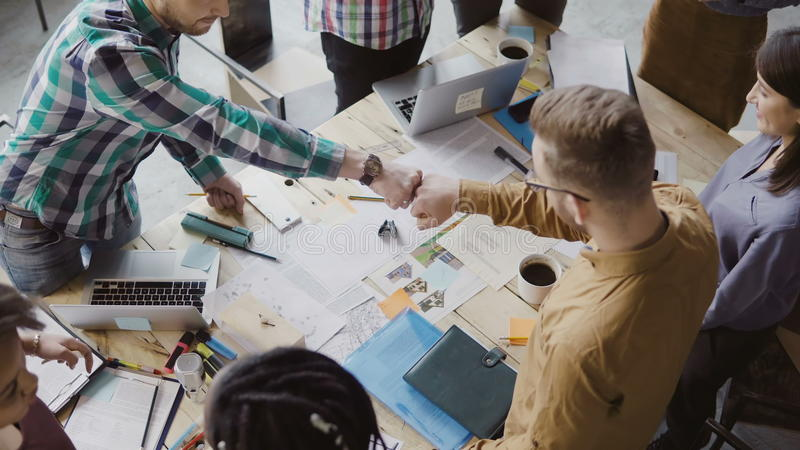 Top view of young business team working together near the table, brainstorming. Two mans fist greeting each other. Mixed race group of hipster people working royalty free stock photo