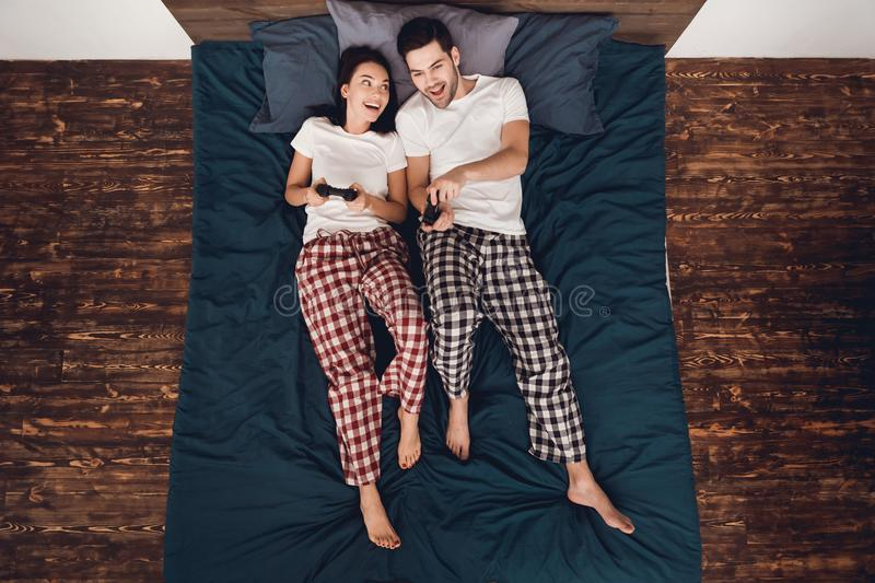 Top view. Young couple in pajamas plays by gamepads in exciting video game, lying on bed in house. stock photos