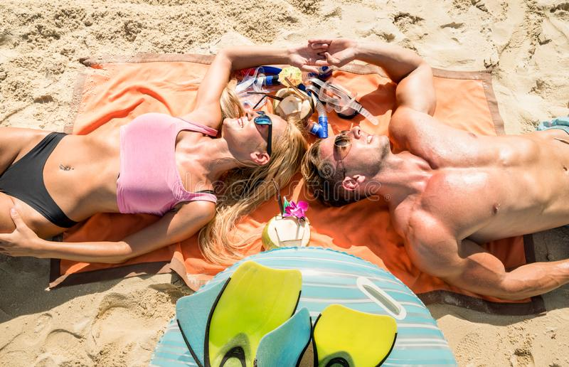 Top view of young couple vacationer having fun and relaxing on tropical Phuket beach in Thailand with coconut drink. Active youth love and travel concept stock images