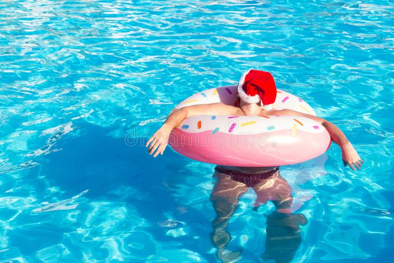 Top view of young drunk guy in christmas hat swim with pink circle in pool. drunk guy on vacation in the hotel royalty free stock image
