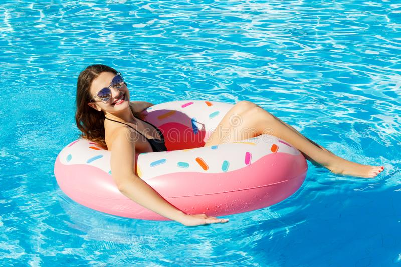 Top view of young female swim with pink circle in pool stock photo