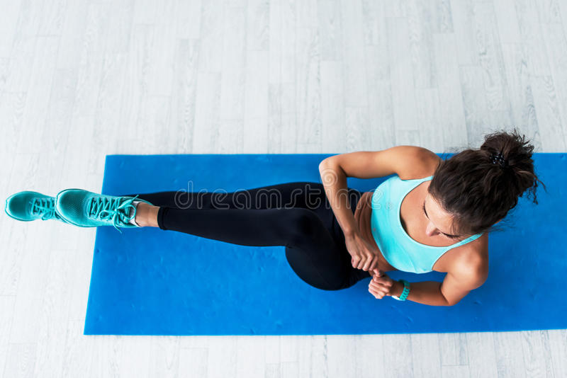 Top view of young fit woman working-out doing bicycle crunches on blue mat indoors. stock photography