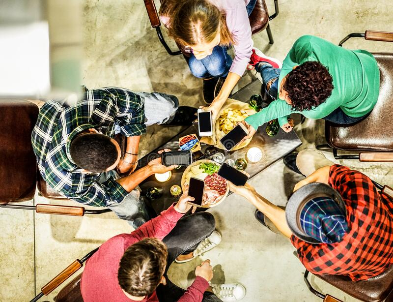 Top view of young friends using mobile smartphones in trendy pub bar brewery - Technology addicted people enjoying appetizer night royalty free stock images