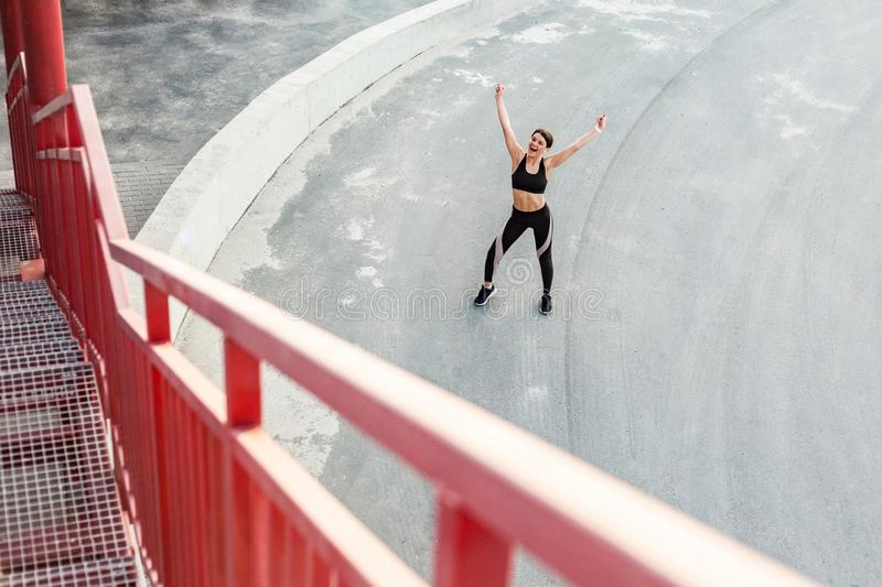 Top view of young happy beautiful sporty girl in black sportwear standing with raised arms and celebrate reaching goal of training stock photo