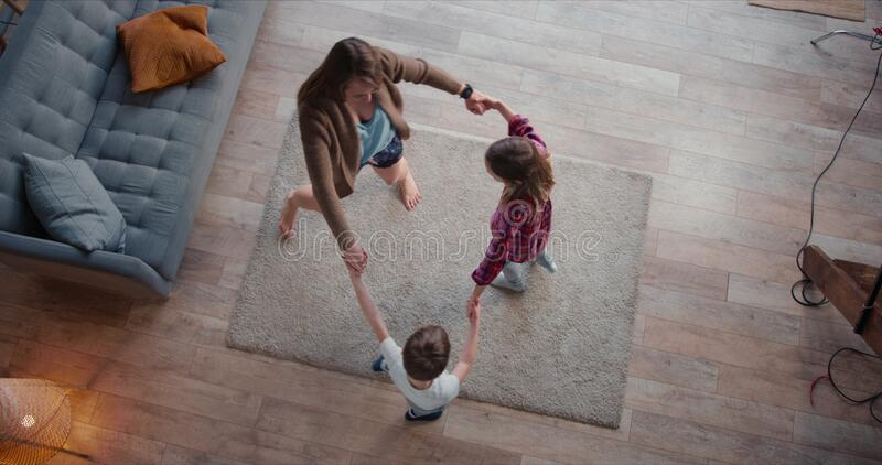 Top view young happy Caucasian mother dancing round dance with two cute teen kids, going crazy on vacation at home. Top view young happy Caucasian m dancing royalty free stock photography