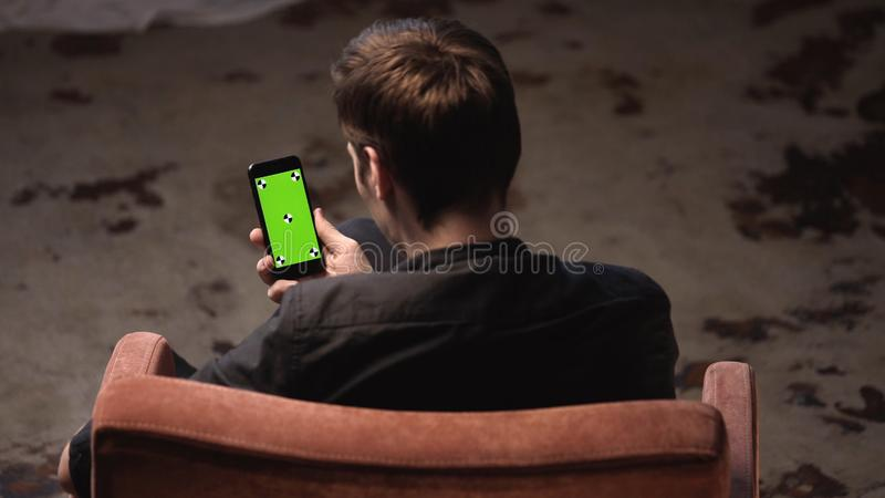Top view of young man with brown hair sitting in chair and tapping on iPhone green screen in dark room. Stock footage royalty free stock photos