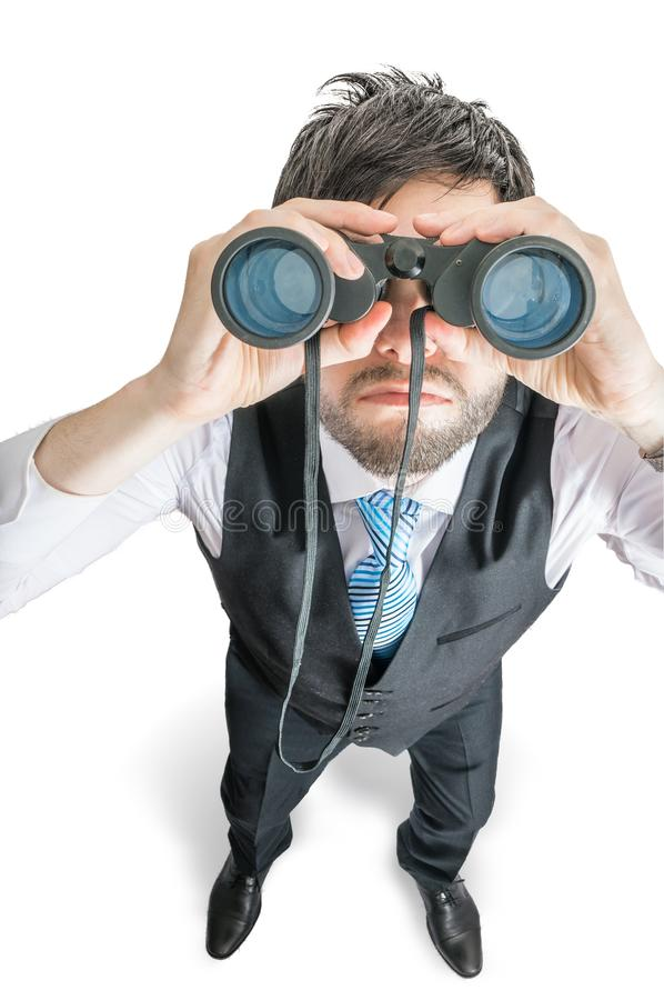 Top view on young man looking in binocular towards you. on white. royalty free stock images
