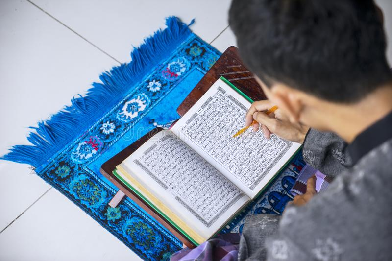 Young man reading Quran after doing Salat royalty free stock photo