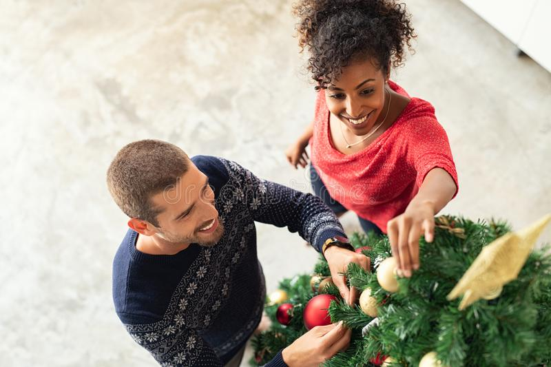 Young couple decorating xmas tree. Top view of young men and african women in sweater adding christmas balls on tree. Happy multiethnic couple decorating royalty free stock photography
