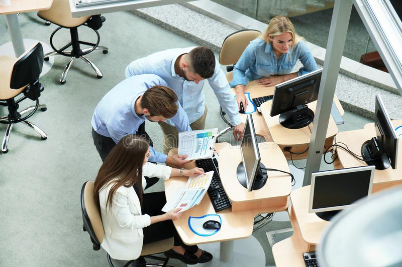 Top view of young modern colleagues in smart casual wear working together while spending time in the office. stock photography