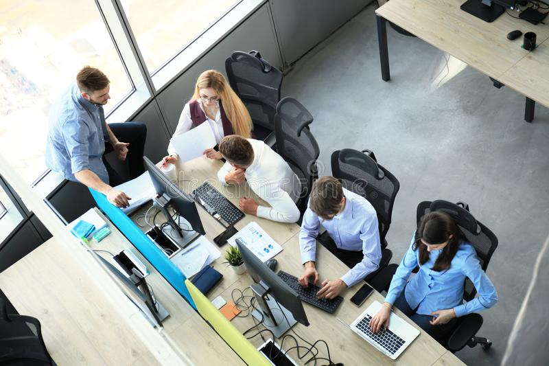 Top view of young modern colleagues in smart casual wear working together while spending time in the office royalty free stock photos