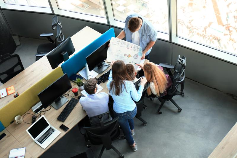Top view of young modern colleagues in smart casual wear working together while spending time in the office. royalty free stock images