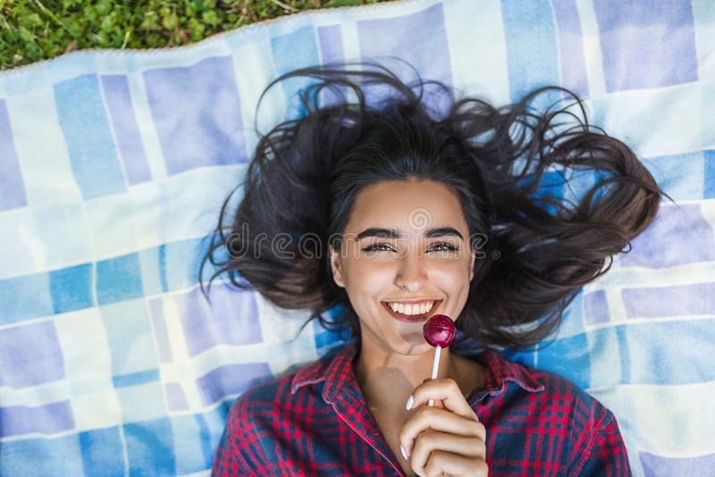 Top view of young brunette woman smiling with lollipop in hand wearing plaid shirt lying on the grass in the park enjoying stock photography