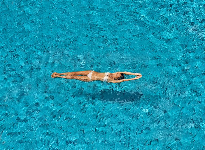 Top view of young slim woman in white bikini relax and floating in infinity swimming pool royalty free stock photo