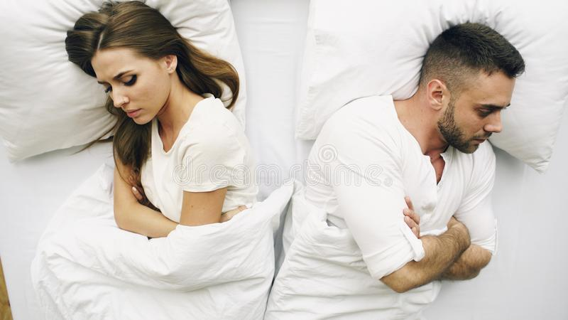 Top view of young upset couple lying in bed have problems after quarrel and angry each other at home royalty free stock images