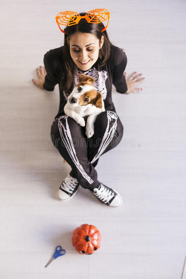 Top view of a young woman with her cute small dog wearing getting ready for Halloween. Woman wearing a skeleton costume. Halloween. Concept. Indoors royalty free stock photos